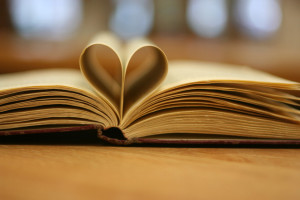 open book with pages folded into a heart