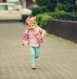 little cute girl running the street